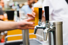 Silver Beer Taps With Black Handles Covered In Condensation With A Hand Serving A Tall Glass Of Amber Coloured Beer In The Background With A Perfect Head