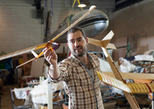 Cheerful Male Aircraft Enthusiast Holding Sports Airplane Models In Workshop