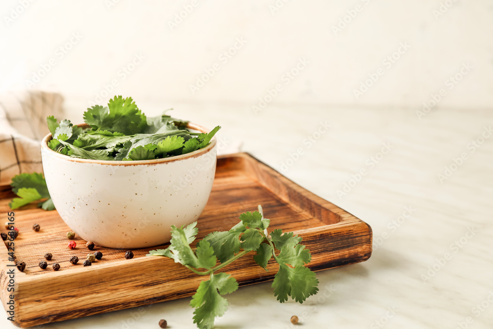 Fototapeta Board with fresh cilantro and peppercorns on light background