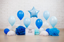 Baby Boy First Birthday Party Decoration - Air Balloons, Paper Balls And Lightbox With One Year Text Over Brick Wall