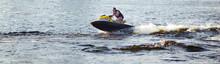 Man Speeding On Jet Ski On Lake During Summer Vacation