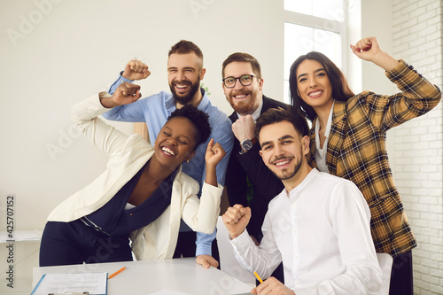 Multinational diverse happy creative business team raising fists making yes gesture celebrating victory feeling excited looking at camera. Win, success, unbelievable achievement and triumph concept