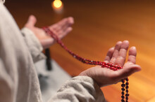Male Hands Hold Red Rosary For Prayer And Practice In A Dark Room By Candlelight