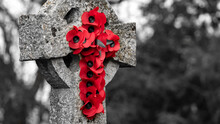 A Wreath Of Poppies Hung On A Gravestone Cross For Remembrance, Image Desaturated To Highlight The Poppies