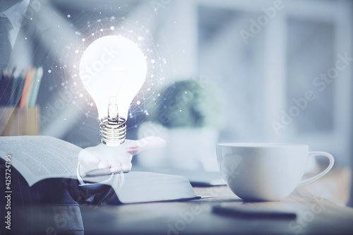 Double exposure of bulb drawing and desktop with coffee and items on table background. Concept of ideas.