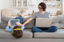 Family, Quarantine, Distance Job Concept. Happy Mother Freelancer Remote Work From Home Office On Laptop During Lockdown, Sitting On Couch, Little Son Playing On Digital Tablet And Wear Headphones.