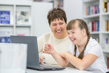 Smiling Girl With Down Syndrome Is Uses A Laptop With Her Teacher At Library. Education For Disabled Children Concept
