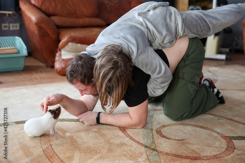 Canvas Print Dad and daughter play with pet guinea pig
