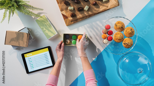Obraz Top view of unrecognizable woman packing biscuits, processing orders desktop concept. - fototapety do salonu