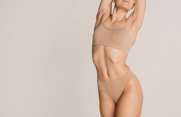 Beautiful female body in nude color underwear over grey background.