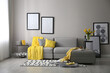 Stylish living room interior with comfortable sofa. Interior design in grey and yellow colors