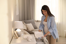 Pregnant Woman Taking Bodysuit From Commode At Home