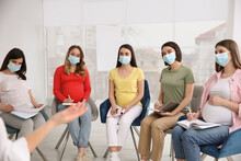 Group Of Pregnant Women And Midwife In Protective Masks At Courses For Expectant Mothers Indoors