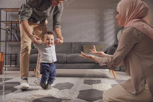Stampa su Tela Happy Muslim family with little son in living room