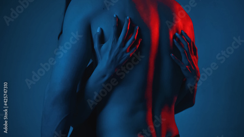 Obraz cropped view of woman scratching back of shirtless man on blue - fototapety do salonu