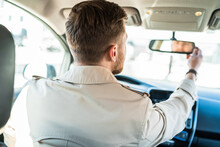 Driver Looks In The Rearview Mirror. Man Adjusts The Mirror In The Car
