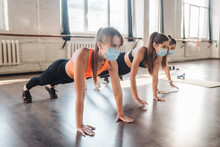 Young Women Doing Push Up Exercise In Room During Morning