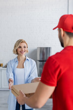 Joyful, Blonde Woman Taking Pizza Boxes From Arabian Courier On Blurred Foreground