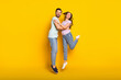 Full length body size view of attractive trendy cheerful couple jumping hugging isolated over bright yellow color background