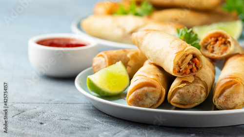 Foto Fried spring rolls with sweet chili sauce and lime on plate