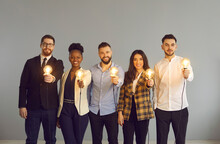 Diverse Multinational Business Team Holding Light Idea Bulb Show New Good Smart Idea Thinking And Creative Innovation. Smiling Positive Businesspeople, Colleagues Group Look At Camera Studio Portrait