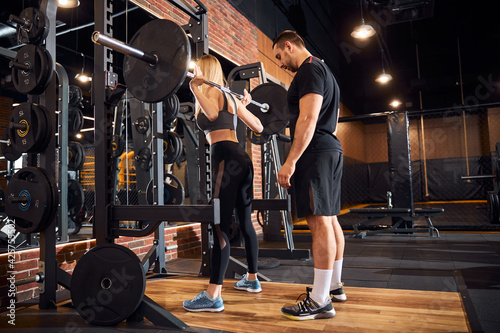 Fototapeta Professional gym instructor assisting woman at the gym obraz