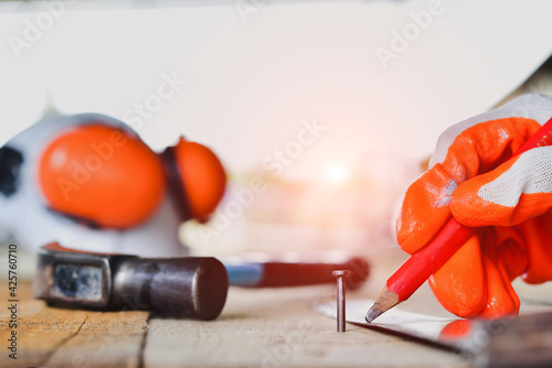 Fotografia, Obraz Nails are hammered on wood in construction Hand holding a pencil for maintenance