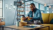 Leinwandbild Motiv Handsome Black African American Man Using Smartphone while Sitting on a Sofa in Cozy Living Room. Freelancer Working From Home. Browsing Internet, Using Social Networks, Having Fun in Flat.