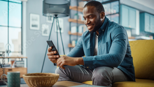 Photo Handsome Black African American Man Using Smartphone while Sitting on a Sofa in Cozy Living Room
