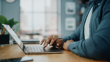 Close Up On Hands Of A Black African American Man Working On Laptop Computer While Sitting Behind Desk In Cozy Living Room. Freelancer Working From Home. Browsing Internet, Using Social Network.