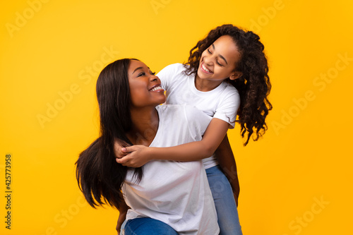 Canvastavla African American girl hugging her smiling mom from behind
