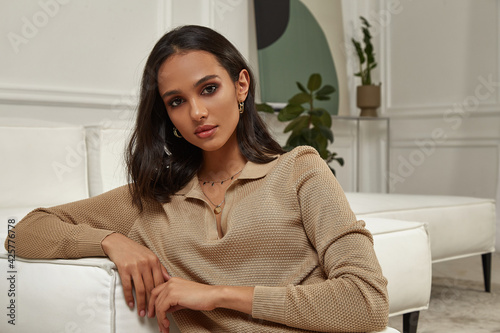 Fashion beautiful model sexy pretty lady dark tanned skin woman brunette hair wear white pants clothes casual office style or romantic date or party in decoration designer room home or hotel.