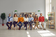 Group Of Serious Multiracial People In Casual Wear Sitting On Row Of Chairs In Spacious Room. Diverse Multiethnic Audience Listening To Speaker During Educational Work Seminar In Modern Office Space