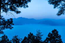 A View Of Mountains And Valley Covered In Early Morning Fog And Mist With Trees Framing The Corners Of The Image