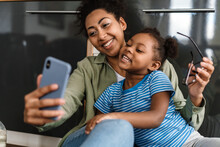 Black Smiling Mother And Daughter Taking Selfie On Mobile Phone