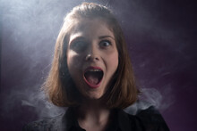 Portrait Of A Surprised Young Girl, Opening Her Mouth, Laughing, Against The Background Of The Smoke Of A Viper