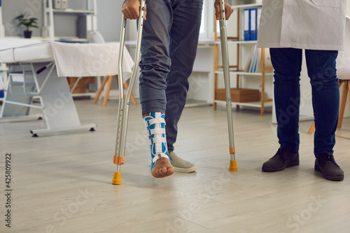 Canvas Midsection of male patient with injured broken leg in orthopedic bandage walking with crutches under doctor control