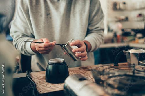 Tableau sur Toile Barista measure coffee powder and brewing black moka coffee using moka coffee maker
