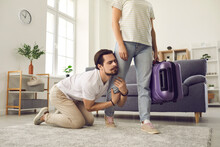 Young Married Couple Breaking Up. Angry Woman Leaving Home With Packed Suitcase. Clingy Desperate Husband On Floor Holding Wife's Leg Begging His Love To Stay. Relationship Breakup And Divorce Concept