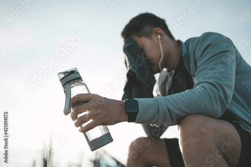 Fotografia, Obraz sport man sitting after running and holding water bottle drink