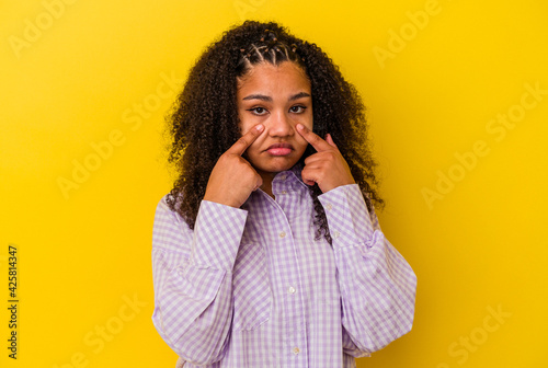 Obraz na plátně Young african american woman isolated on yellow background crying, unhappy with something, agony and confusion concept