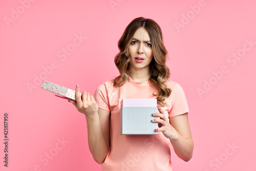 Tablou Canvas Young woman disappointed with her gift box on pink background