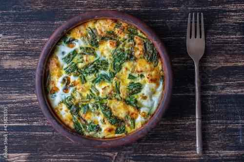 Ceramic bowl with vegetable frittata, simple vegetarian food. Frittata with egg, pepper, onion, cheese and green wild garlic leaves on table