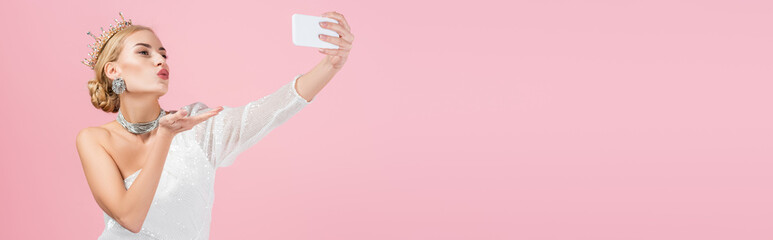 blonde woman in luxury crown taking selfie on smartphone and sending air kiss isolated on pink, banner