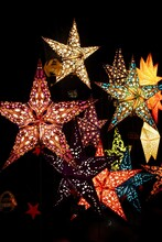Brightly Lit Star Lanterns With A Black Background. Photo Taken At A German Christmas Market Kiosk.