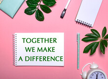 TOGETHER WE MAKE A DIFFERENCE Is Written In Green On A White Notepad On A Pink Background Surrounded By Notepads, Pens, White Alarm Clock And Green Leaves. Educational Concept