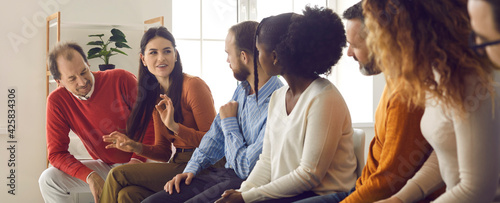 Foto Diverse people sitting on row of chairs and talking