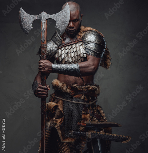 Fearful african soldier with axe stares at camera in dark background