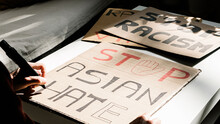 Unrecognizable Male Activist Making Placards Against Asian Racism Due To Coronavirus At Home. Equal Rights Concept