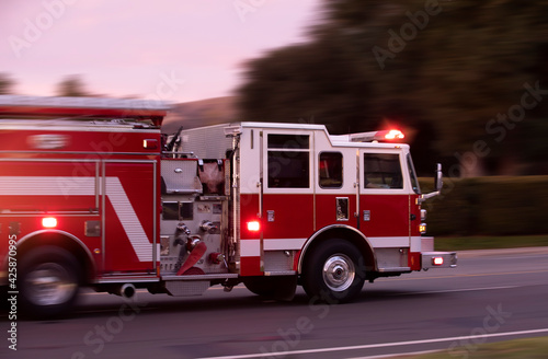 Fototapeta A fire engine races to the scene of an emergency.